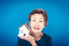 住宅模型を持った老女